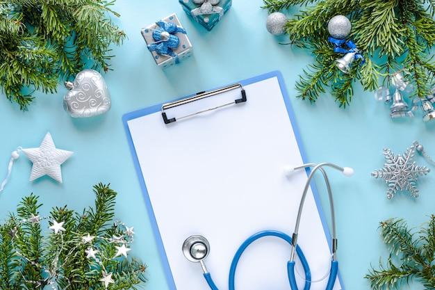 Stethoskop, thermometer, leere zwischenablage und weihnachtsdekoration