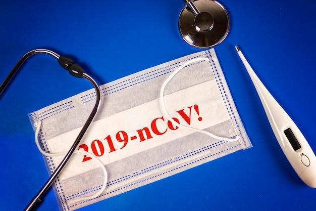 Stethoskop, thermometer und thermometer medizinische maske mit 2019-ncov-text auf blauem hintergrund. neuartiges coronavirus - 2019-ncov, wuhan-viruskonzept.