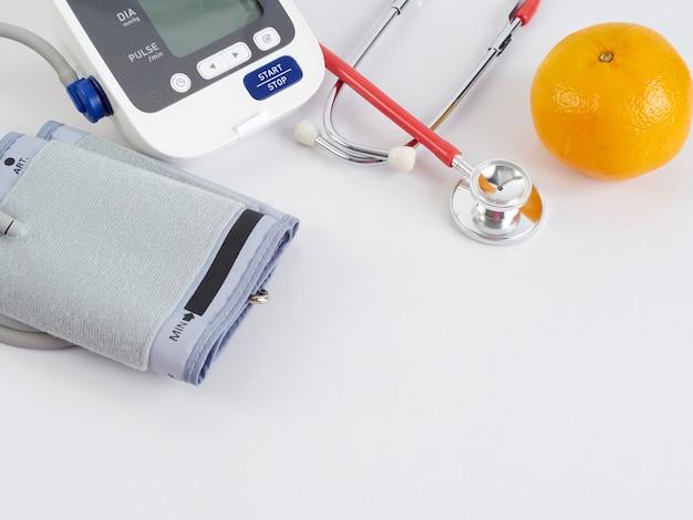 Stethoskop und automatisches blutdruckmessgerät mit orangen