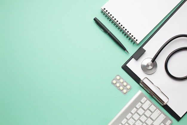 Stethoskop und blisterpackung der pille mit büroartikel über grünem hintergrund