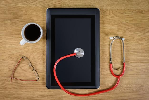 Stethoskop und digitale tablette am schreibtisch des doktors