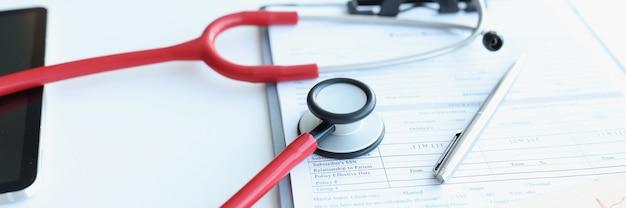 Stethoskop und elektrokardiogramm, die auf der krankengeschichte des patienten liegen, nahaufnahme. kardiologisches versorgungskonzept
