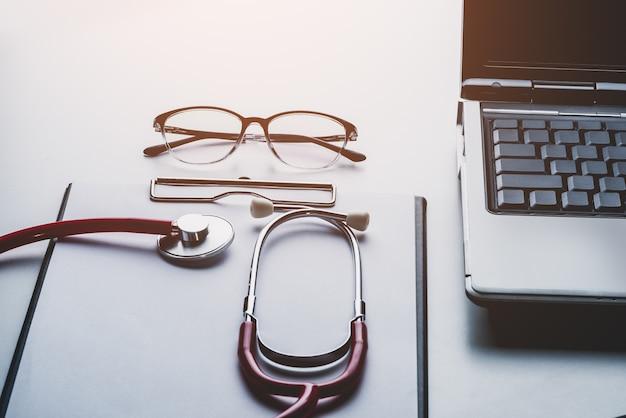 Stethoskop und gläser auf laptop mit leerem papier des klemmbrettes