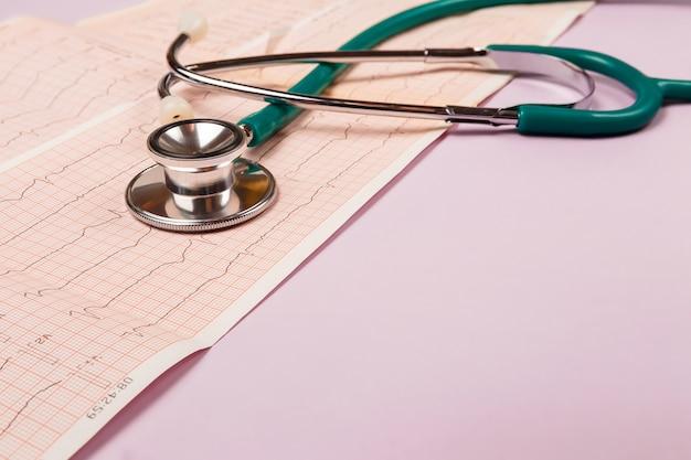 Stethoskop und kardiogramm des herzens auf einem rosa tisch. unten ist platz für die inschrift.