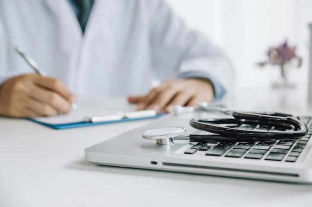 Stethoskop und laptop auf schreibtisch, doktor, der im krankenhaus schreibt eine verordnung arbeitet