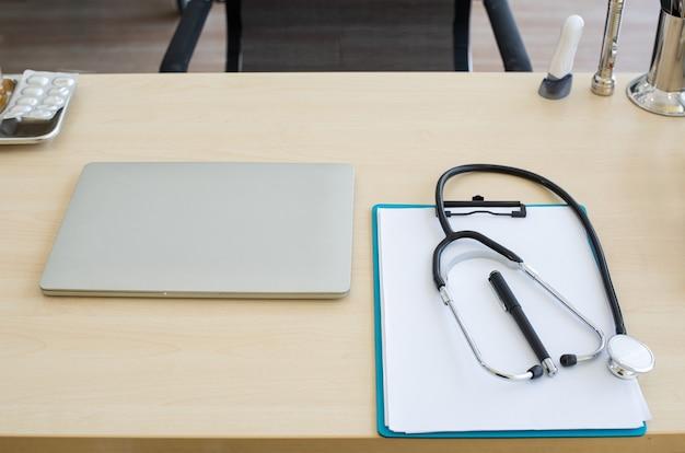 Stethoskop und laptop und anderes medizinisches objekt auf tisch des arztes.