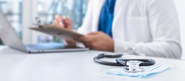 Stethoskop und medizinische maske auf dem schreibtisch des arztes