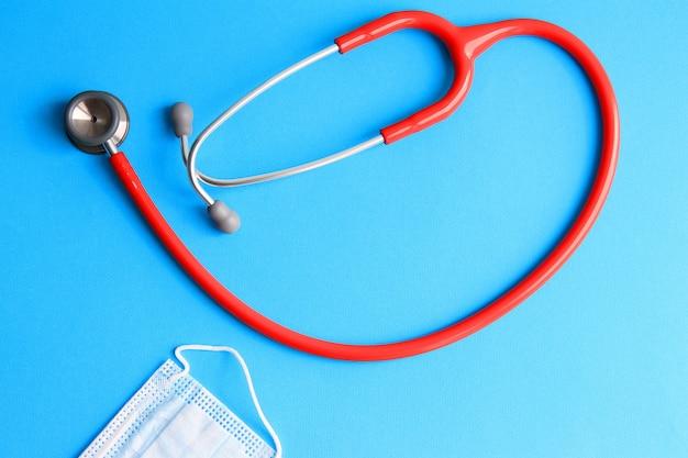 Stethoskop und medizinische maske auf einem blauen hintergrund konzept der medizin, gesundheit, krankheit.