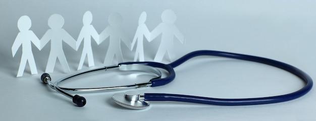Stethoskop und papiermänner auf dem tisch. das konzept der familienmedizin