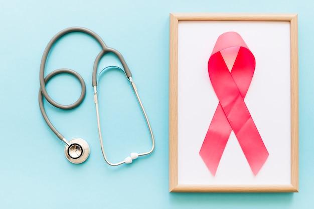 Stethoskop und rosa band auf weißem holzrahmen über den farbigen hintergrund