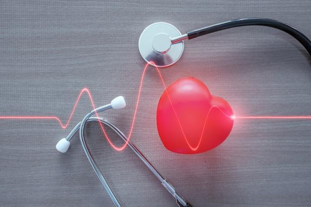 Stethoskop und rotes herz mit glühender roter herzwelle.