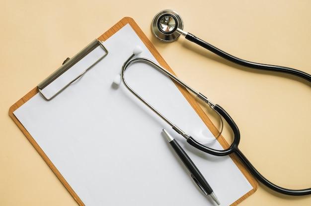 Stethoskop und stift über dem klemmbrett mit leerem weißbuch auf beige hintergrund