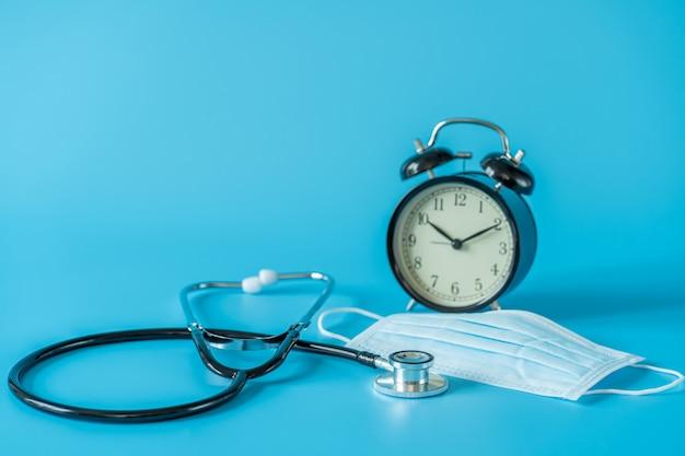 Stethoskop und vintage-uhr auf blauem raum. medizin- und gesundheitskonzept