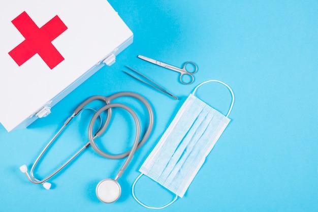 Stethoskop und weißer verbandskasten und medizinische ausrüstung auf leerem blauem hintergrund