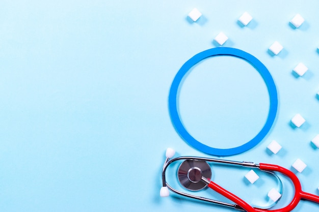 Stethoskop und zuckerwürfel auf blauem pastellhintergrund. weltdiabetestagskonzept
