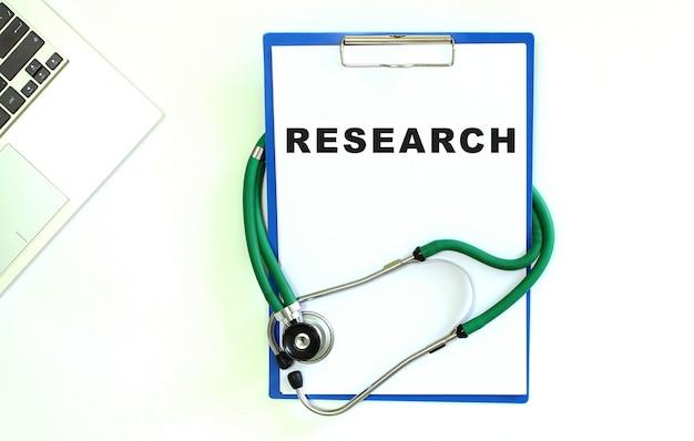 Stethoskop und zwischenablage mit leerem weißem blatt papier.