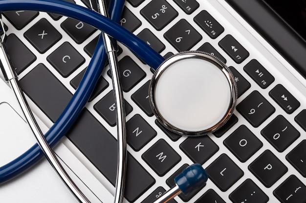 Stethoskopkopf, der auf computertastatur-nahaufnahme liegt. medizinisches konzept. modernes medizin- und high-tech-ausstattungskonzept