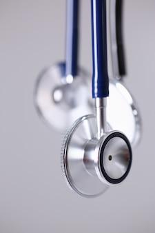 Stethoskopkopf, der auf grauer hintergrundnahaufnahme liegt