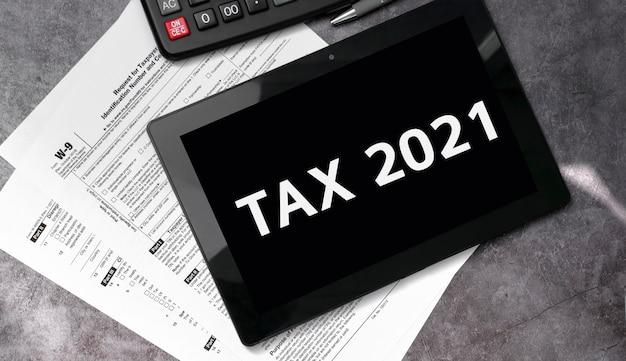 Steuer 2021 auf einem schwarzen tablett und mit steuerformularen und taschenrechner