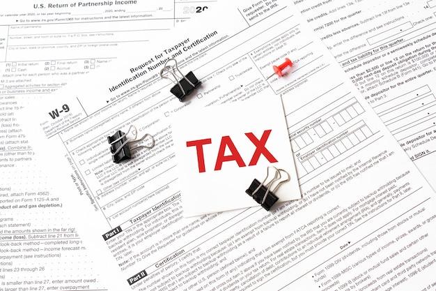 Steuer geschrieben auf weißem aufkleber mit büroklammer zum steuerformular