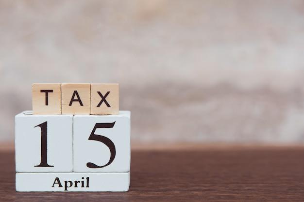 Steuer mit 15. april. alphabet und kalender holzblockwürfel mit nummer auf tisch dunkle planke aus holz mit kopierraum