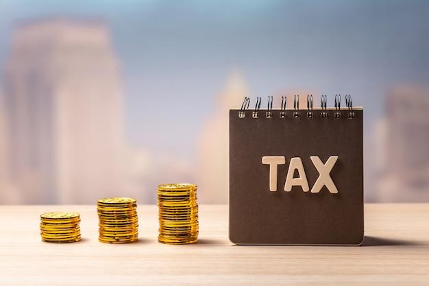 Steuerbeschriftung auf notizbuch und stapel von münzen