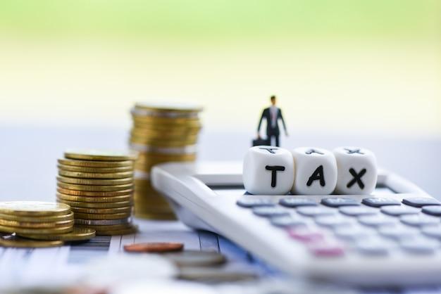 Steuerfinanzgeschäftsmannrechner stapelte münzen auf rechnungsrechnungspapier für die zeitsteuer, die gezahlte schuldzahlung füllt