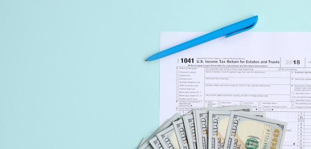 Steuerformular 1041 liegt nahe hundert dollarscheinen und blauem stift