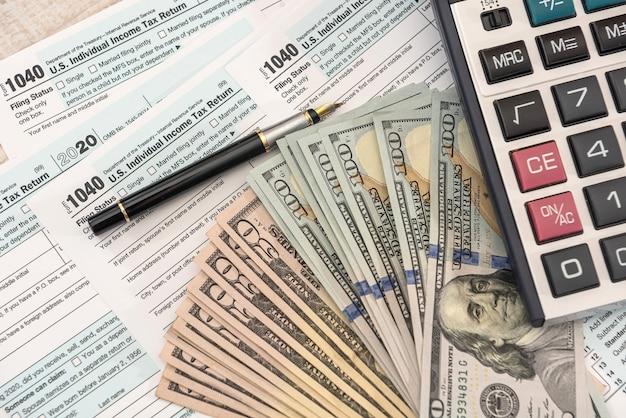 Steuerformulare 1040 mit dollar und rechner zum ausfüllen im april. steuern konzept.
