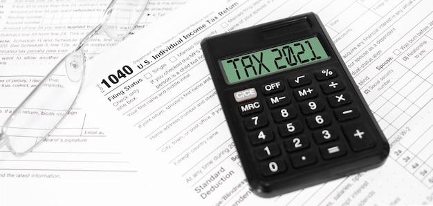 Steuerformulare 1040, taschenrechner mit schild tax 2021 und stift auf dem tisch