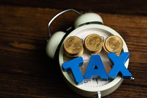 Steuern sie alphabet mit stapel der münze und des weinleseweckers
