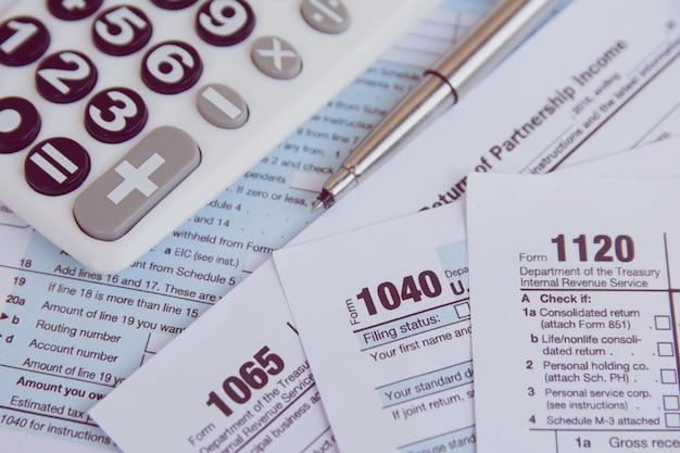 Steuersaison. taschenrechner, stift auf us-steuerformular