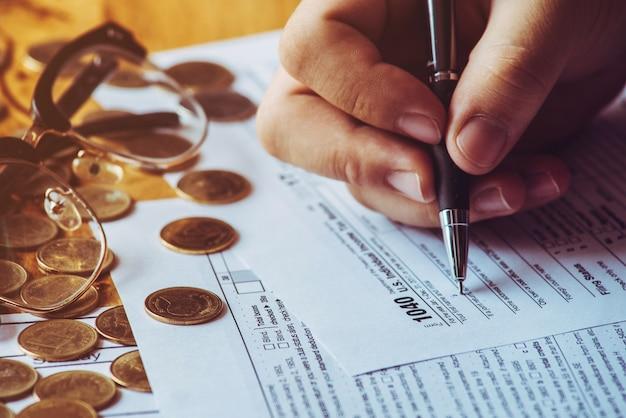 Steuertag. einreichung des us-steuerformulars. steuerformular uns geschäft einkommen büro hand füllen konzept.