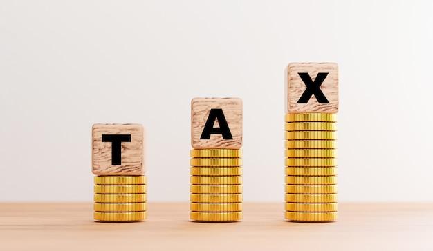 Steuertext-druckbildschirm auf holzwürfelblock beim zunehmenden stapeln von goldmünzen für das steuerzahlungskonzept durch 3d-rendering.