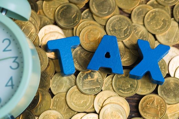 Steuerwort mit stapel von münzen und vintage wecker