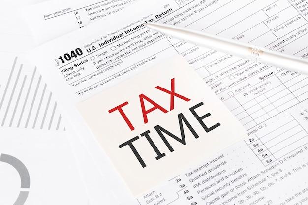 Steuerzeit geschrieben auf gelbem aufkleber mit büroklammer zum steuerformular