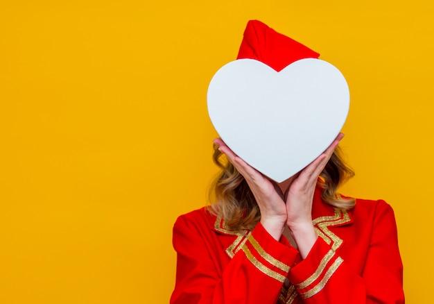 Stewardess, der in der roten uniform mit herzformfeiertags-gfit kasten trägt