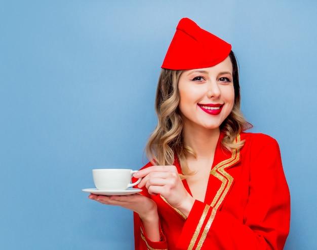 Stewardess, der in der roten uniform mit tasse kaffee oder te trägt