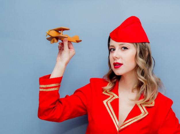 Stewardess, die in der roten uniform mit hölzernem flugzeug trägt