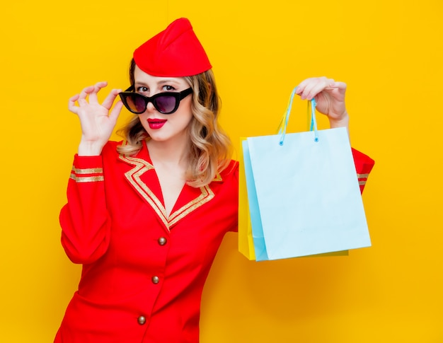 Stewardess in roter uniform mit einkaufstüten.