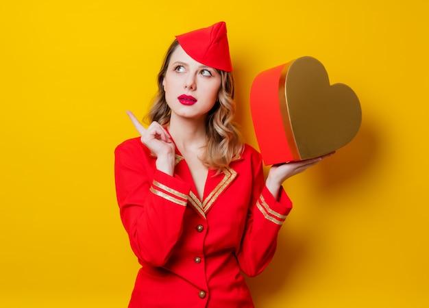 Stewardess in roter uniform mit herzförmigem geschenkkarton