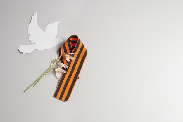 Stgeorges-band ist in form einer neun gefaltet.in der nähe ist eine weiße taube und eine schneeglöckchenblume