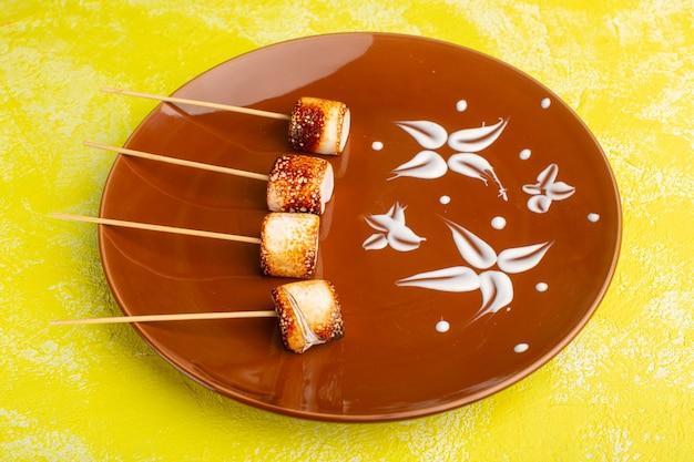 Stick confitures in brauner platte auf gelbem hintergrund snack foto farbe lebensmittel mahlzeit