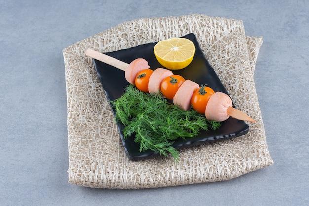 Stick kebab wurst und kirschtomate.