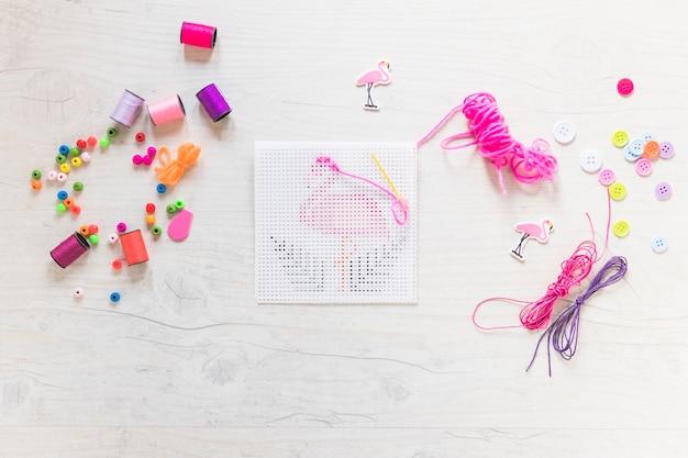 Stickereikreuzstich mit glasschlackengewinde und dekorative elemente auf strukturiertem hintergrund
