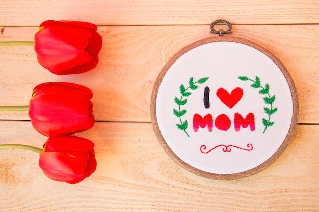 Stickgeschenk für mama. stickerei auf dem rahmen, als eine art handarbeit, kreativität und kunst. sicht von oben.