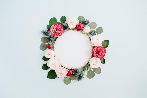 Stickrahmen mit beige rosa blütenknospen auf blassem pastellblauem hintergrund. flache lage, ansicht von oben
