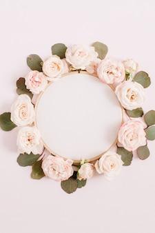 Stickrahmen mit beigen rosenblütenknospen lokalisiert auf hellem pastellrosa