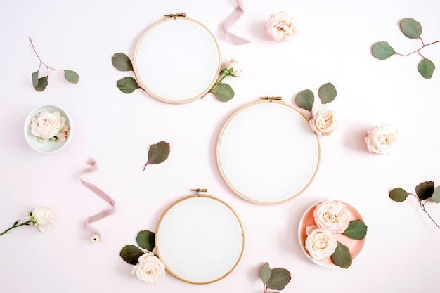 Stickrahmen mit beigen rosenblütenknospen und eukalyptus auf hellem pastellrosa
