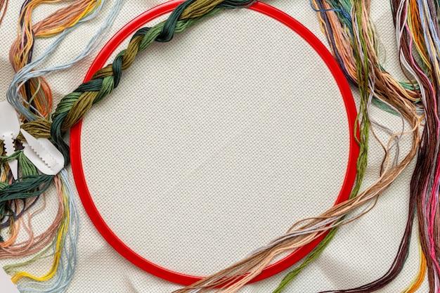 Stickrahmen, stickset mit farbfäden und leinwandhintergrund mit kopierraum